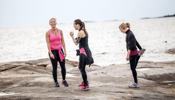 Tre löpare som stretchar på en klippa