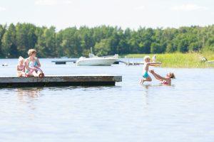 Barn och vuxna som badar från en brygga i Västerviks skärgård