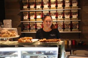 En person bakom en kafédisk full med bakverk.